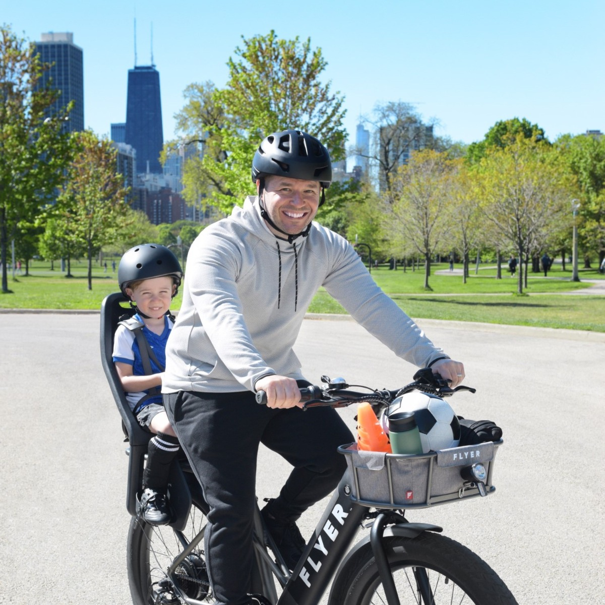 Father and son riding electric bike in the park