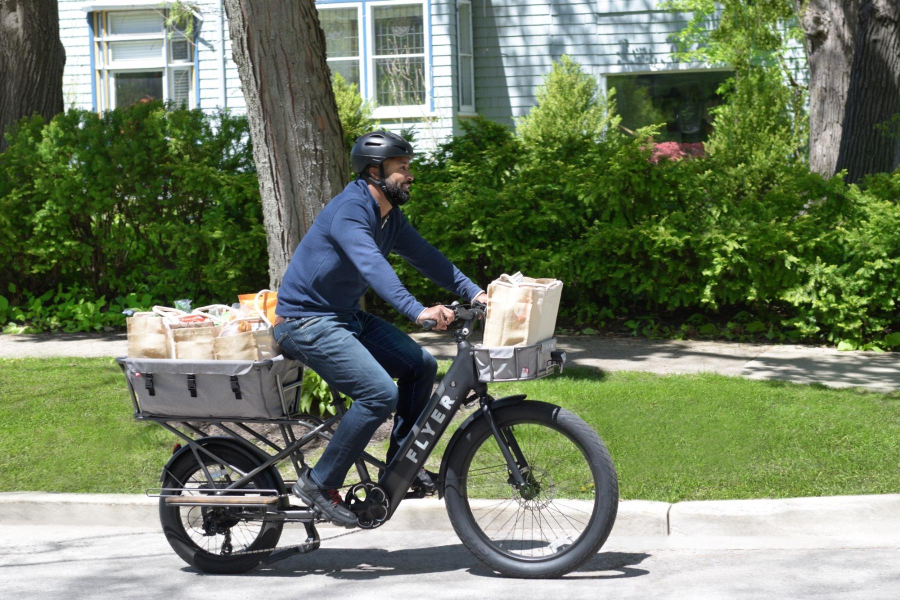 Man riding Flyer L885 black electric bike through suburban street with groceries