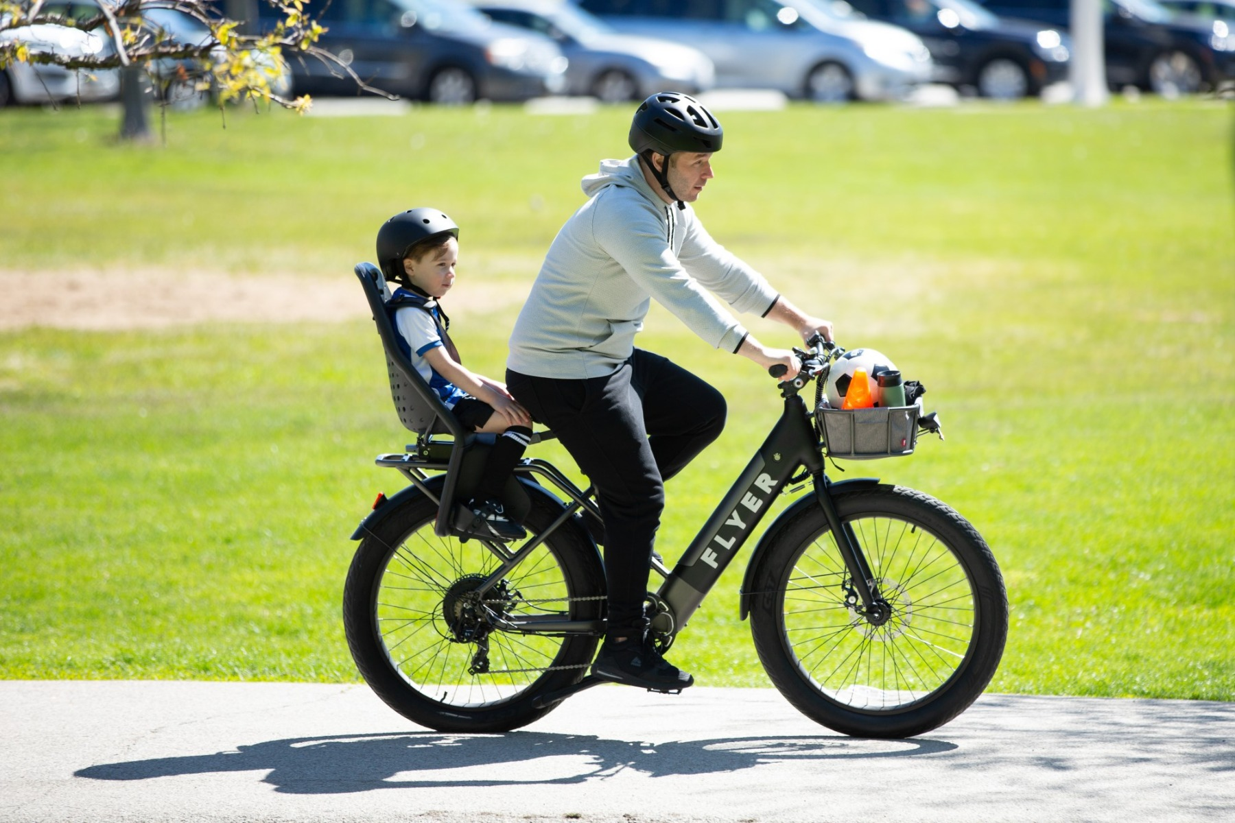 Father and son riding Flyer M880 black electric bike through the park using throttle only mode