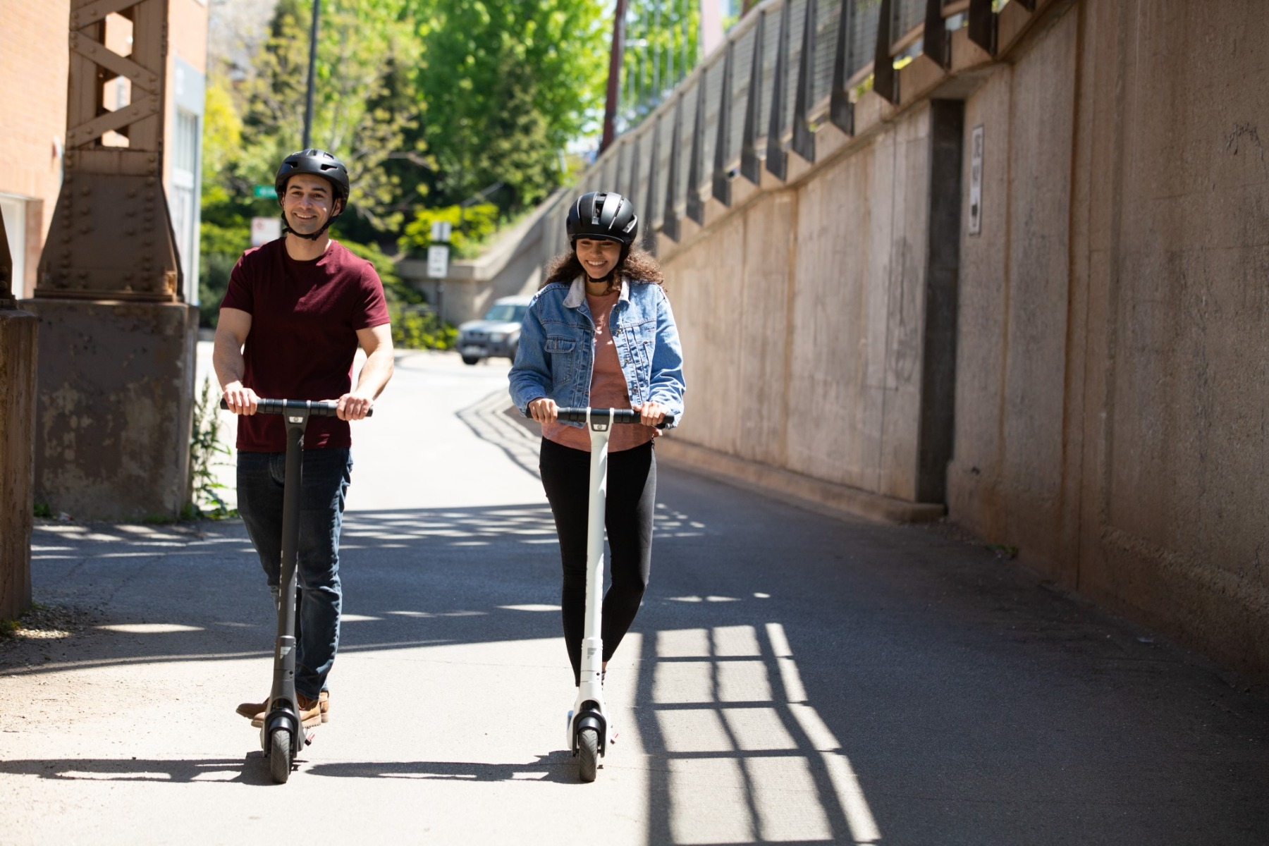 Two adults riding Flyer S533 electric scooters in the city