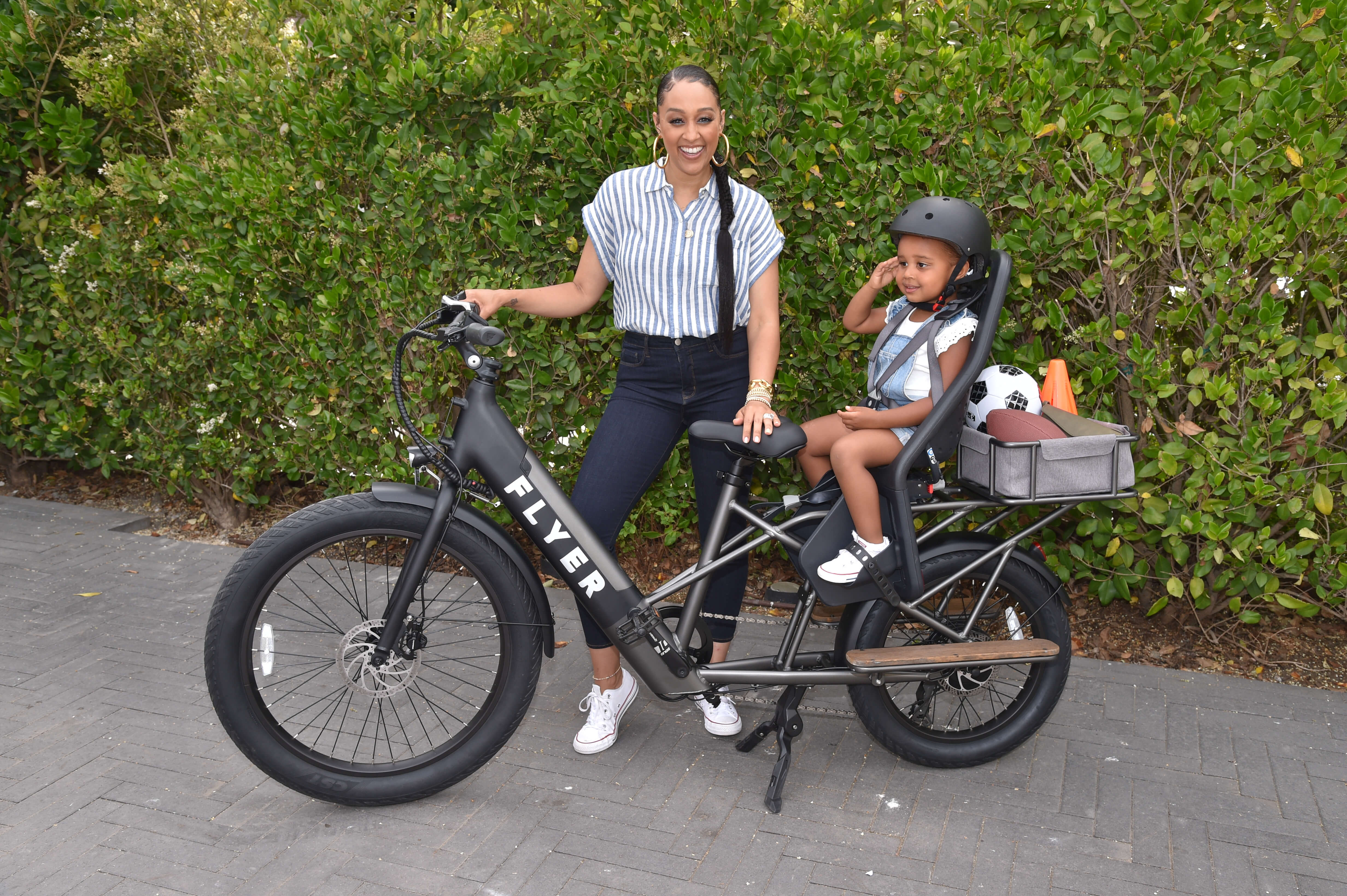 Tia Mowry and daughter posing with Flyer L885 black electric bike