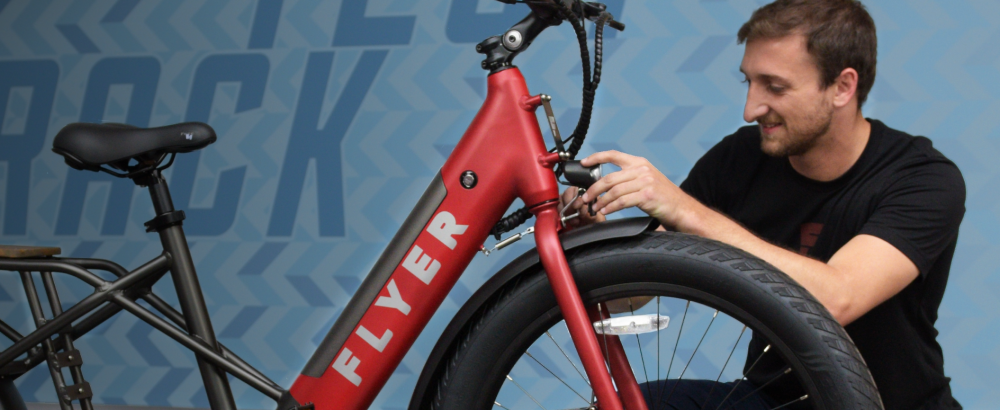 Member of the Radio Flyer service team reviewing a red Flyer electric bike